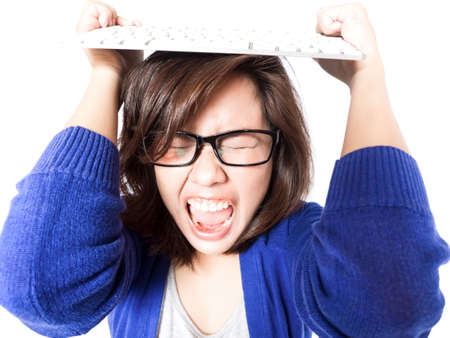 Isolated portrait of young stress woman with computer keyboard on white background. Pretty eyeglasses female model angry. photo