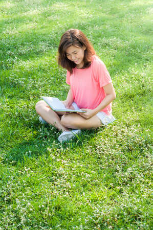 outsides: beautiful woman reading a book in the garden Stock Photo