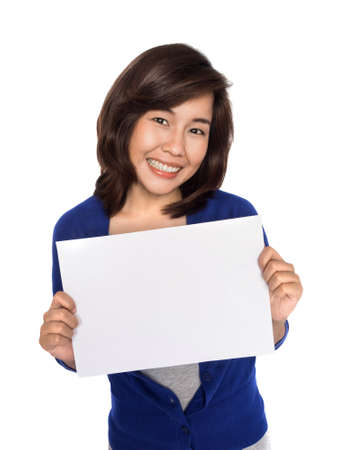Woman showing sign. Cute casual young beautiful woman showing blank white sign isolated on white background waist up.