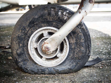 stuck up: Old rusty dusty flat tire. Stock Photo