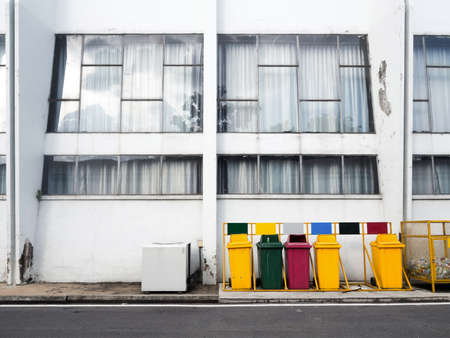 Different colored bins at side of building. photo