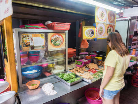 KUALA LUMPUR, MALAYSIA - NOVEMBER 14, 2014 : People buying food in Chinatown Street hawker cart. Chinatown is very popular with tourists and locals.