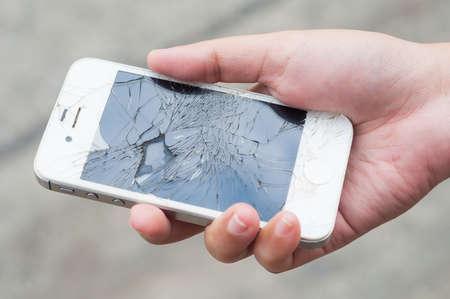 Handen die gebroken mobiele smartphone Redactioneel
