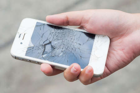 cristal roto: Manos que sostienen el teléfono inteligente móvil roto