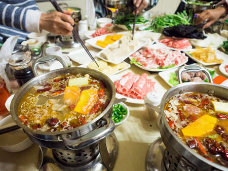 mouth watering: Chinese dinning dip sliced meat in chilli hot soup with chopsticks, shabu shabu