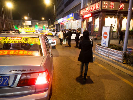 discontinued: Dalian, China - January 18 ,2015: People calling taxis on the road at night. The number of taxis in Dalian reaches 12,000. Many are them are Volkswagen Santana and Jetta, discontinued models in Europe.
