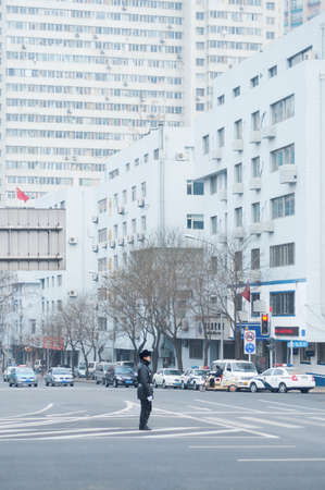 Dalian, China January 18, 2015: Traffic policeman directing cars in a crossing road
