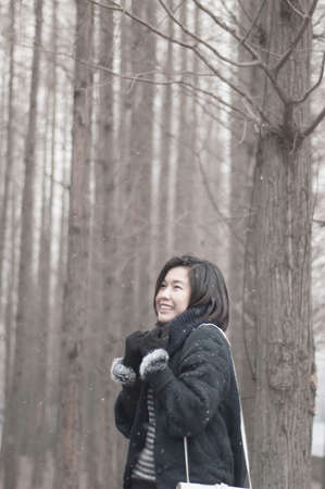A beautiful asian girl in winter pine forest. photo