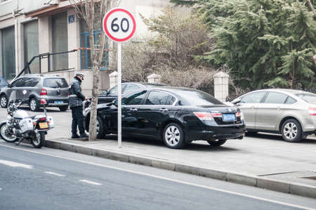 Dalian, China January 18, 2015: Dalian police officer writing parking ticket. Editorial