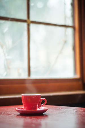 Red mug coffee and window, Winter tone.