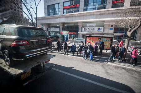 mercedes: Dalian, China January 19, 2015: Chinese people waiting the bus while new Mercedes Benz SUV delivering on truck has passed. Editorial