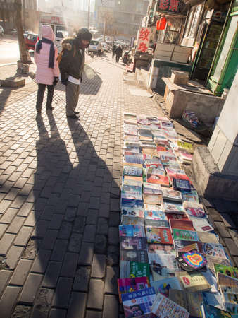 second hand: Dalina, China - January 19, 2015: People searching for second hand books on the street in China.