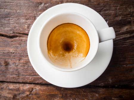 gulp: Empty espresso coffee cup on wood table.