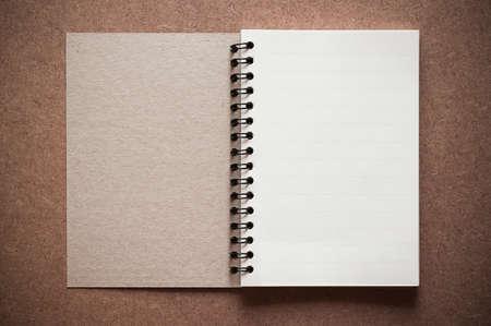 Blank spiral binder notebook on wooden background. photo