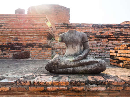 destroyed: Destroyed Buddha statue with old dilapidated temple in background , Ayuthaya, Thailand