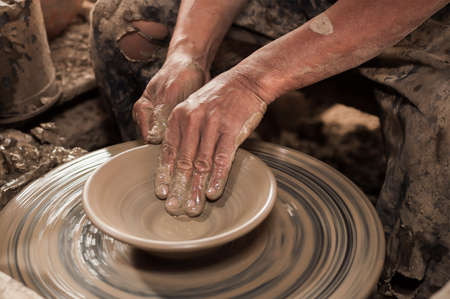 clay craft: Artisan hands making clay pot