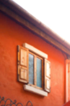 saturate: Blur background image of wooden window on saturate orange wall house.