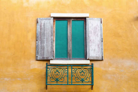 saturate: Background image of wooden window on saturate yellow wall house.