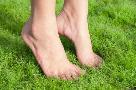 Woman feet tiptoe over green grass.