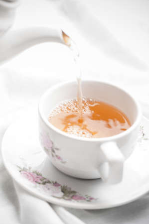 teaparty: Tea being poured into tea cup on white table cloth background.