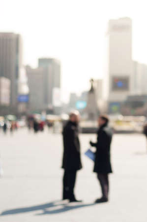 Two businessman chatting converstion on street with city building background photo
