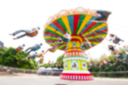 chain swing ride: Blur background image of people enjoy roller swings in amusement park.