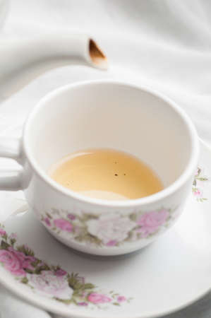 teaparty: Tea being fill into empty tea cup on white table cloth . Stock Photo