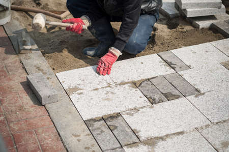 Construction worker installing the pavestone on the road