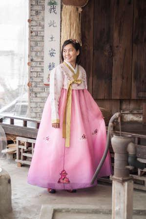 korean fashion: Beautiful asian woman in Hanbok Korean dress .Smiling in traditional house background.