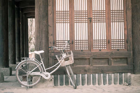 chinese wall: Bicycle parking against asian style house vintage color processed filter.