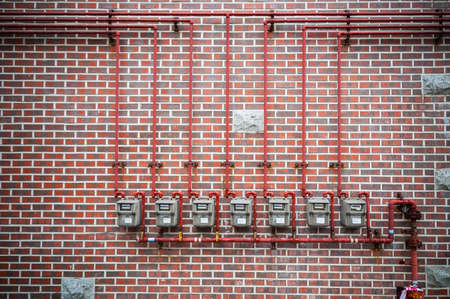 Row of residential natural gas meters and pipe on brick wall Stock Photo