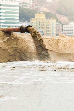 greenpeace: Draining mud water with city building on background. Stock Photo