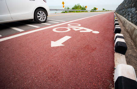 urbanism: Bicycle lane with car moving pass. Stock Photo