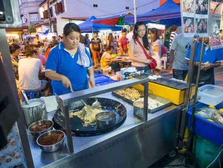 Malacca Malaysia  November 15 2014: Street food vendor making stir fried food at Jonker street in Malacca.