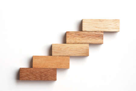 concepto: Madera de apilamiento de bloques como escalón. Concepto de negocio para el proceso de crecimiento de éxito.