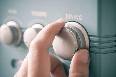 communication: Bouton radio fm de réglage à la main. Rétro image traitée.