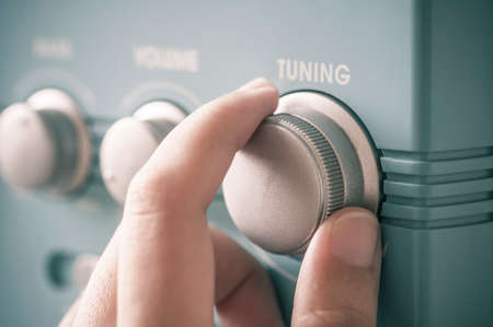 interaction: Hand tuning fm radio button. Retro image processed. Stock Photo