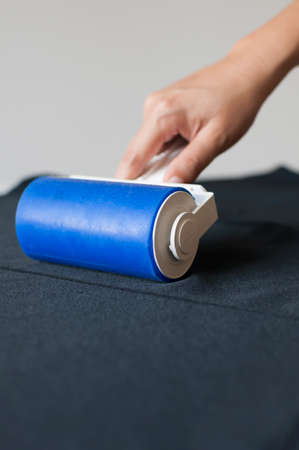 lint: Lint roller on black cloth. Stock Photo