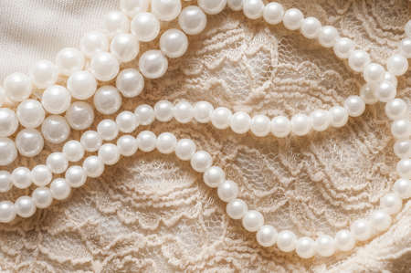 Pearl necklace on lace clothes background. Archivio Fotografico