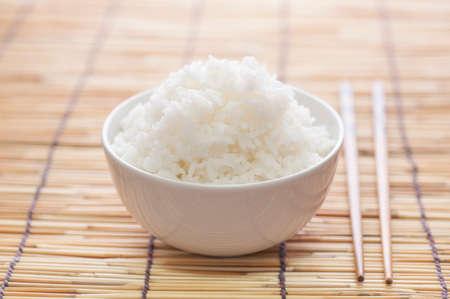 Rice bowl on bamboo mat with chopsticks Stockfoto
