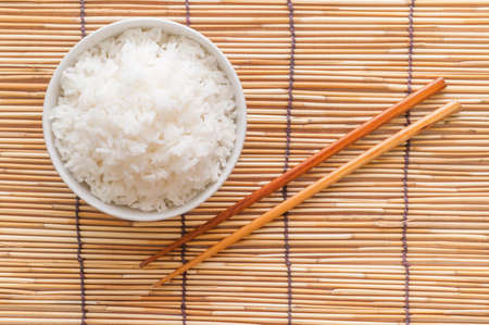 Rice bowl on bamboo mat with chopsticks Stock Photo