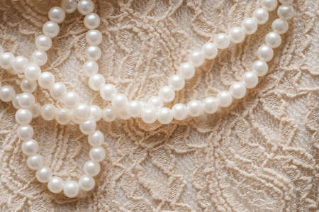 Pearl necklace on lace clothes background. Stock Photo