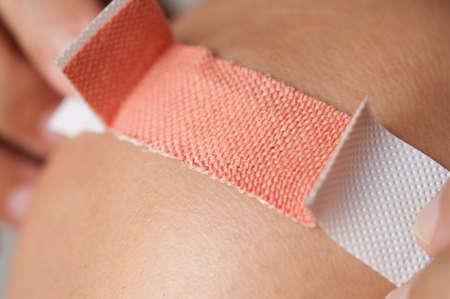 hands on knees: Applying adhesive bandage on knee