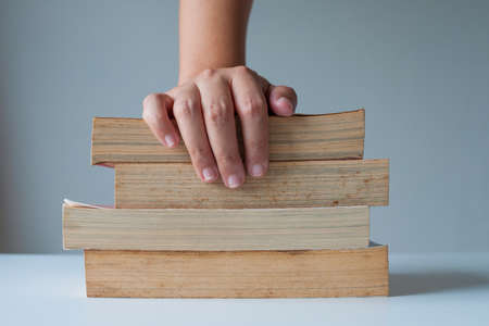 hard to find: Stack of old books with hand catching. Stock Photo