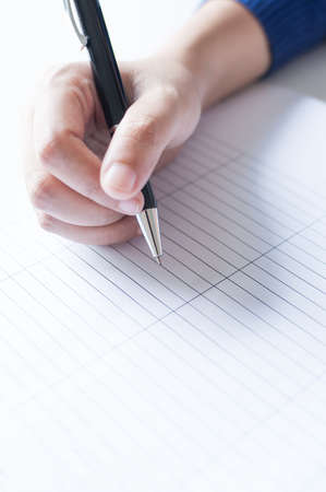 Female hands with pen writing on paper with table list.