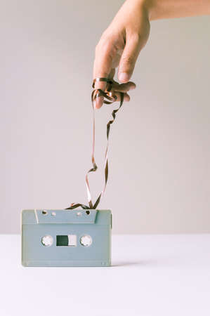 tape: Hand over messy tape from retro cassette. Stock Photo