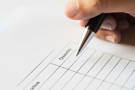 Female hands with pen writing on paper with quantity table list. Stock Photo
