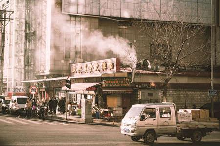 traffic building: Dalian, China - January 19, 2015: People and traffic around commercial building around Dalian trains station. Retro image processed