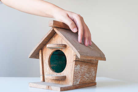 economic rent: Hand over wood bird house. Low budget house concept.
