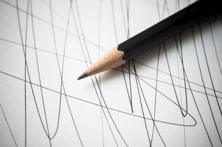 pencil and paper: Pencil on paper with black curved lines. Shallow depth focus.